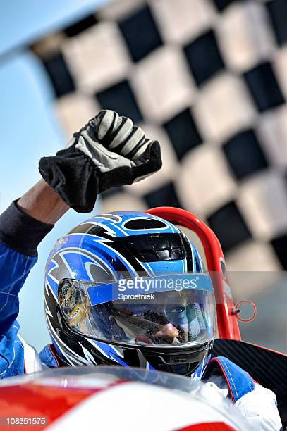 winning racing driver against flag - race car driver stock pictures, royalty-free photos & images