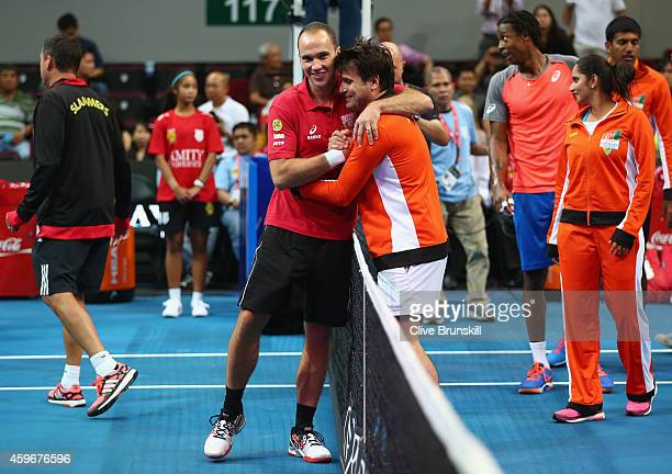Winning team coach/player Fabrice Santoro of the Indian Aces is congratulated at the net by Bruno Soares of the Singapore Slammers at the end of the...