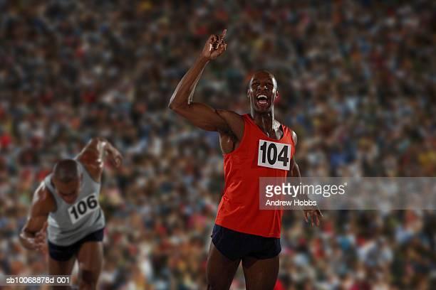 Winning track runner cheering in stadium