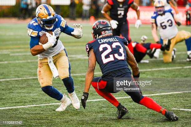 Winnipeg Blue Bombers Running back Andrew Harris tries to avoid a tackle by Tommie Campbell during the Winnipeg Blue Bombers versus the Montreal...
