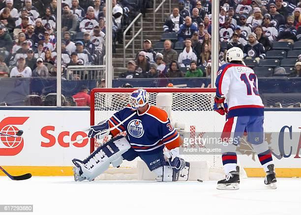 Winnipeg Jets alumni get the puck past Bill Ranford of the Edmonton Oilers alumni during the 2016 Tim Hortons NHL Heritage Classic alumni game at...