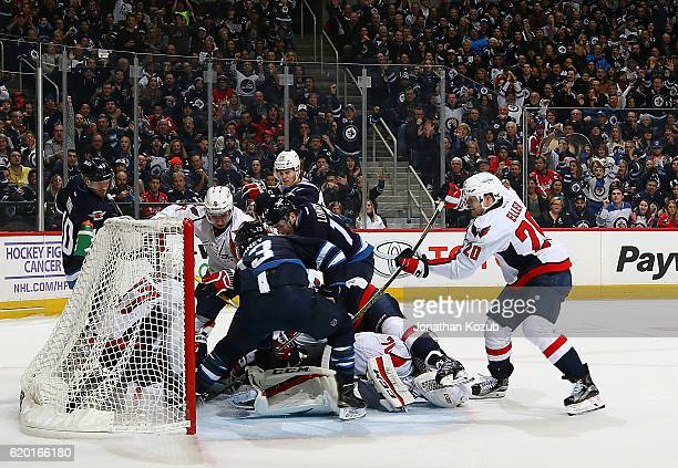 Winnipeg Jets and Washington Capitals players crash the crease as the Jets try to get the puck past goaltender Braden Holtby during second period...
