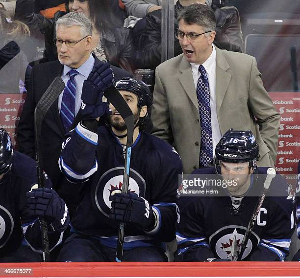 Winnipeg Jets' assistant coach Perry Pearn and head coach Claude Noel react from the bench as players Chris Thorburn and Andrew Ladd watch during...