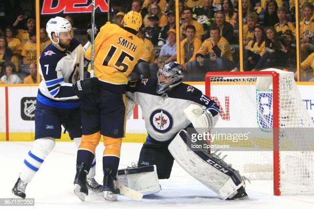 Winnipeg Jets defenseman Ben Chiarot and Nashville Predators right wing Craig Smith battle for position in front of Winnipeg Jets goalie Connor...