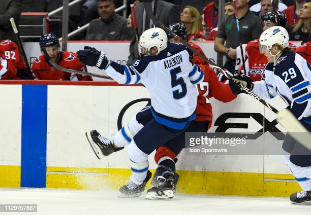 Winnipeg Jets defenseman Dmitry Kulikov hits Washington Capitals center Travis Boyd in the first period on March 10 at the Capital One Arena in...