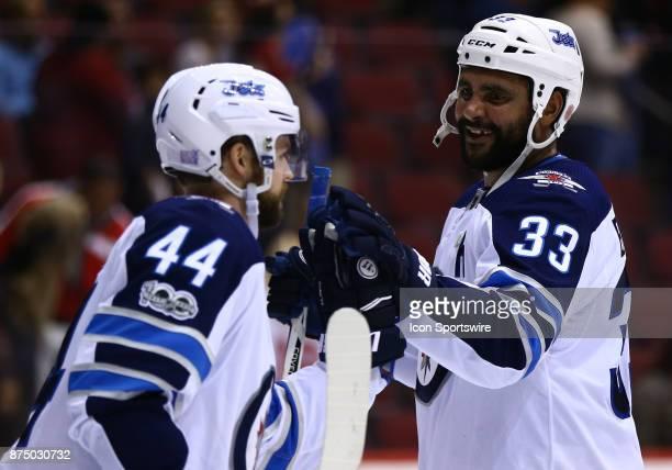 Winnipeg Jets defenseman Dustin Byfuglien and Winnipeg Jets defenseman Josh Morrissey shake hands after winning the NHL hockey game between the...