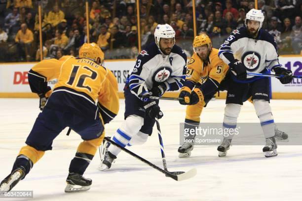Winnipeg Jets defenseman Dustin Byfuglien skates with the puck as Nashville Predators center Mike Fisher and Nashville Predators winger Austin Watson...