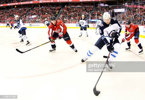 Winnipeg Jets defenseman Jacob Trouba works the puck against Washington Capitals right wing TJ Oshie and left wing Jakub Vrana in the first period on...