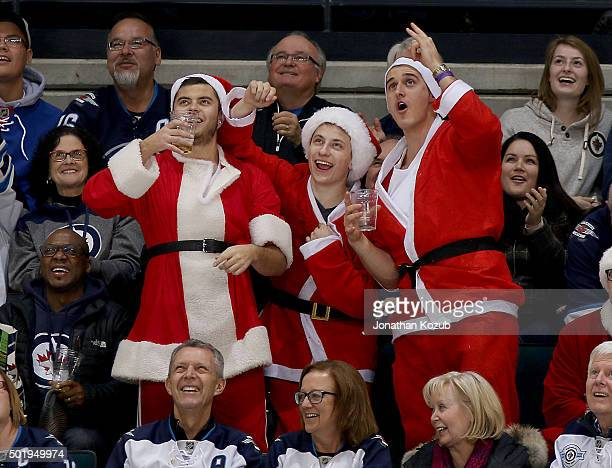 Winnipeg Jets fans all dressed as Santa Claus celebrate in the stands during third period action between the Jets and the New York Rangers at the MTS...