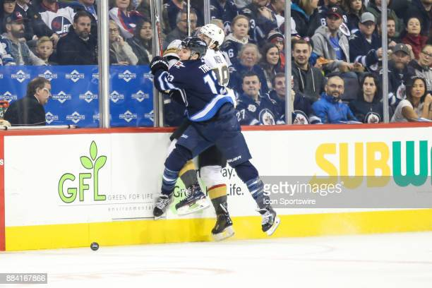 Winnipeg Jets forward Brandon Tanev bodies Vegas Golden Knights defenseman Nate Schmidt during the NHL game between the Winnipeg Jets and the Vegas...
