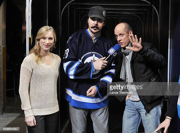 Winnipeg Jets Game Night Host Dave Wheeler interviews Canadian figure skaters Kurt Browning and Joannie Rochette during a stoppage in play between...