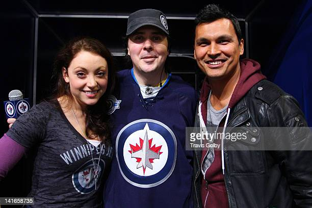 Winnipeg Jets Game Night Host Dave Wheeler poses with actor Adam Beach and his girlfriend Leah Gibson during NHL action between the Jets and the...