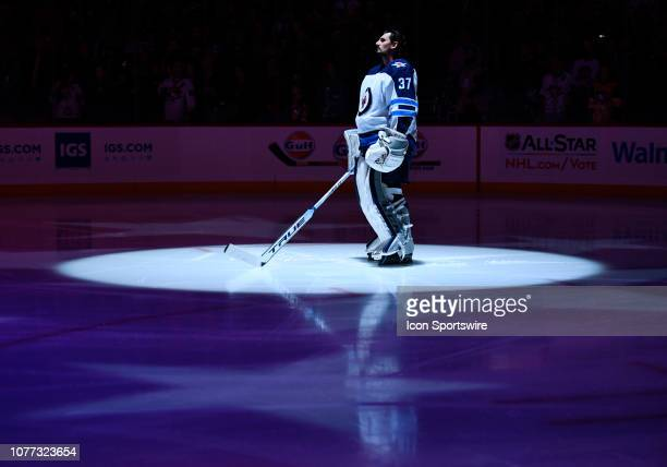 """Winnipeg Jets Goalie Connor Hellebuyck stands in the spotlight during the """"National Anthem"""" before the NHL game between the Pittsburgh Penguins and..."""
