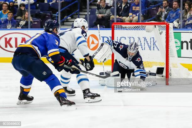 Winnipeg Jets goaltender Connor Hellebuyck right makes a save as St Louis Blues' Vladimir Sobotka left fights for the puck against Winnipeg Jets'...