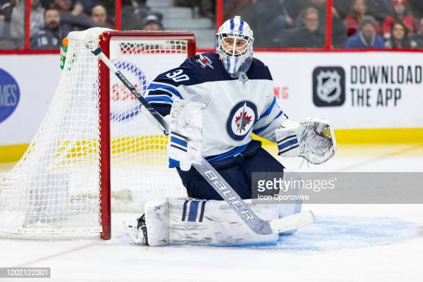 Winnipeg Jets goaltender Laurent Brossoit tracks the play to the side boards during second period National Hockey League action between the Winnipeg...