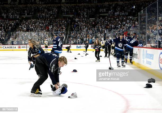 Winnipeg Jets Ice Crew members pick up the hats that litter the ice after the first period hat trick scored by Blake Wheeler against the Pittsburgh...