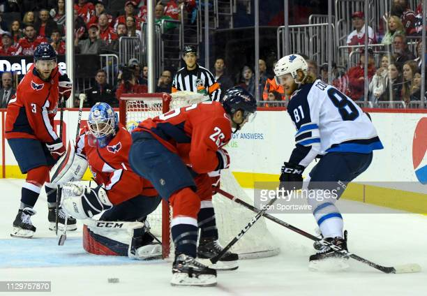 Winnipeg Jets left wing Kyle Connor attempts a first period pass against Washington Capitals center Nic Dowd on March 10 at the Capital One Arena in...