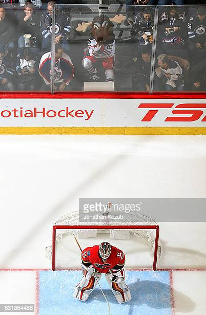 Winnipeg Jets mascot Mick E Moose keeps an eye on goaltender Chad Johnson of the Calgary Flames as he guards the net during second period action at...