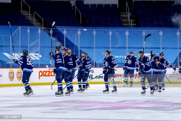 Winnipeg Jets players celebrate with a stick salute as they leave the ice following a 2-1 overtime victory over the Montreal Canadiens at the Bell...