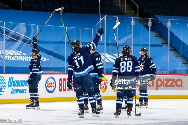 Winnipeg Jets players give a stick salute following a 6-3 victory over the Ottawa Senators at the Bell MTS Place on January 23, 2021 in Winnipeg,...