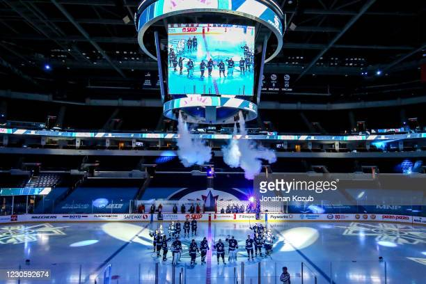 Winnipeg Jets players give a stick salute following the player introductions for the season opener against the Calgary Flames at the Bell MTS Place...
