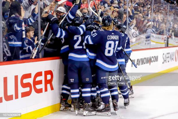 Winnipeg Jets players mob teammate Mark Scheifele after he scored the overtime winning goal against the Tampa Bay Lightning at the Bell MTS Place on...