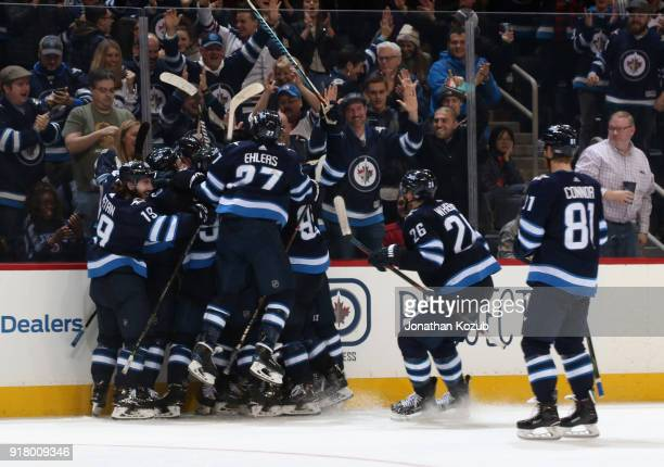Winnipeg Jets players mob Tyler Myers after he scored the overtime winning goal against the Washington Capitals at the Bell MTS Place on February 13...