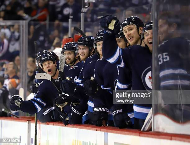 Winnipeg Jets players on the bench celebrate a second period goal by teammate Mathieu Perreault against the San Jose Sharks at the Bell MTS Place on...