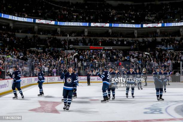 Winnipeg Jets players salute the fans following a 4-3 victory over the Columbus Blue Jackets at the Bell MTS Place on November 23, 2019 in Winnipeg,...