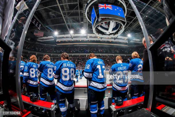 Winnipeg Jets players stand on the bench during a moment of silence for the victims of the terror attack in Christchurch New Zealand prior to NHL...