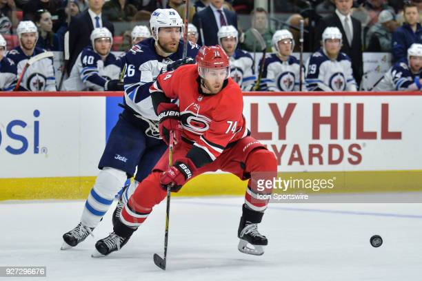 Winnipeg Jets Right Wing Blake Wheeler and Carolina Hurricanes Defenceman Jaccob Slavin skate after a loose puck during a game between the Winnipeg...