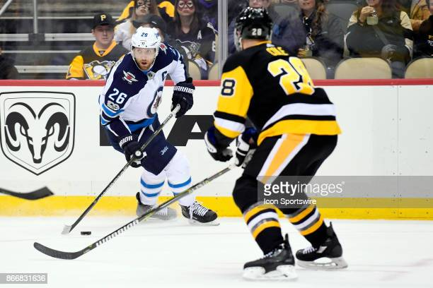 Winnipeg Jets Right Wing Blake Wheeler handles the puck in front of Pittsburgh Penguins defenseman Ian Cole during the first period in the NHL game...
