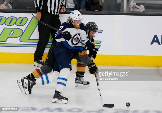 Winnipeg Jets right wing Patrik Laine and Vegas Golden Knights center Ryan Carpenter battle for control of the puck during the third period of Game...