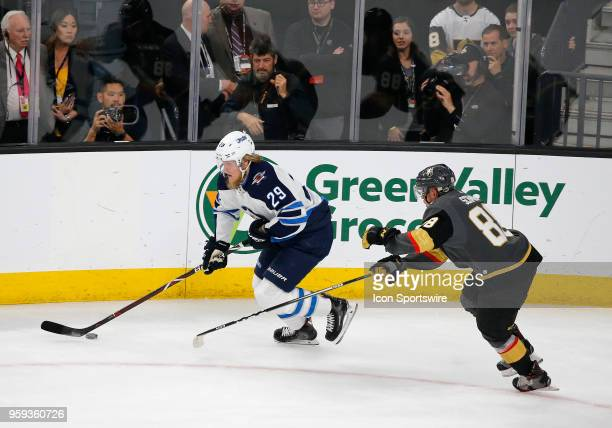 Winnipeg Jets right wing Patrik Laine moves the puck away from Vegas Golden Knights defenseman Nate Schmidt during the second period of Game Three of...