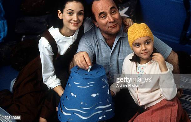 Winona Ryder Bob Hoskins and Christina Ricci gathered around lamp in a scene from the film 'Mermaids' 1990