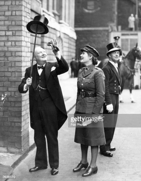 Winston Churchill balancing a top hat on his walking stick watched by his daughter Mary outside the Mansion House in London