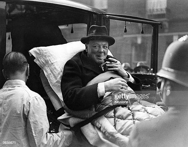 Winston Churchill being carried into his London home on a stretcher following his return from America where he was involved in a motor accident