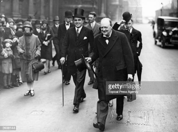 Winston Churchill carrying the red budget briefcase from Downing Street to go to the Houses of Parliament