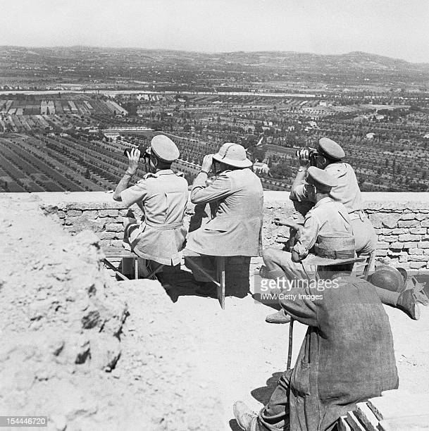 Winston Churchill During The Second World War In Italy, The Prime Minister Winston Churchill uses binoculars to watch an attack on a German-held...