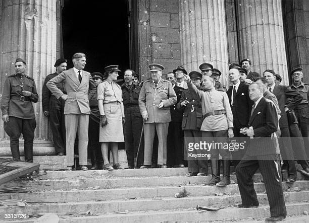Winston Churchill on the steps of the Chancellery Berlin On the left is Anthony Eden and in the centre is Mary Churchill A Russian officer points out...