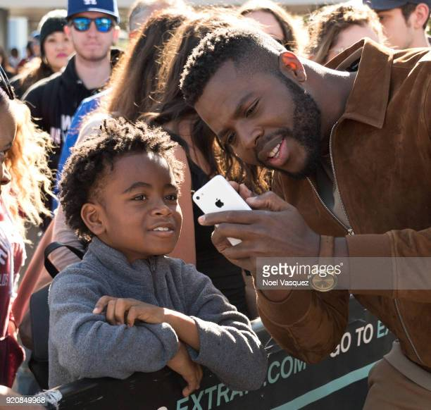 Winston Duke takes a selfie with a fan at 'Extra' at Universal Studios Hollywood on February 19 2018 in Universal City California