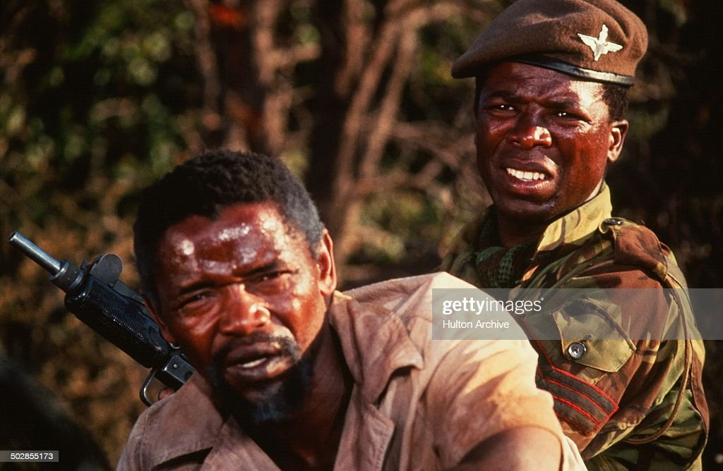 Winston Ntshona and John Kani look on in a scene from the movie 'The Wild Geese' circa 1978.