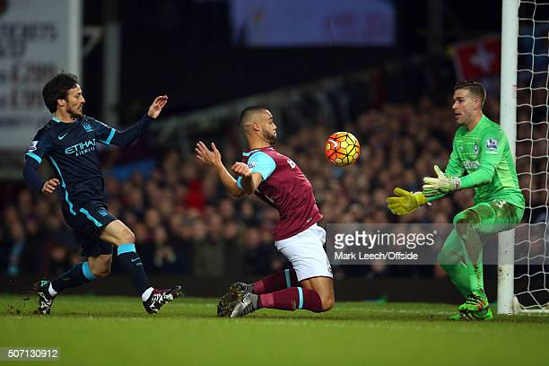 Winston Reid of West Ham chests the ball back to West Ham goalkeeper Adrian as David Silva of Manchester City looks on during the Barclays Premier...