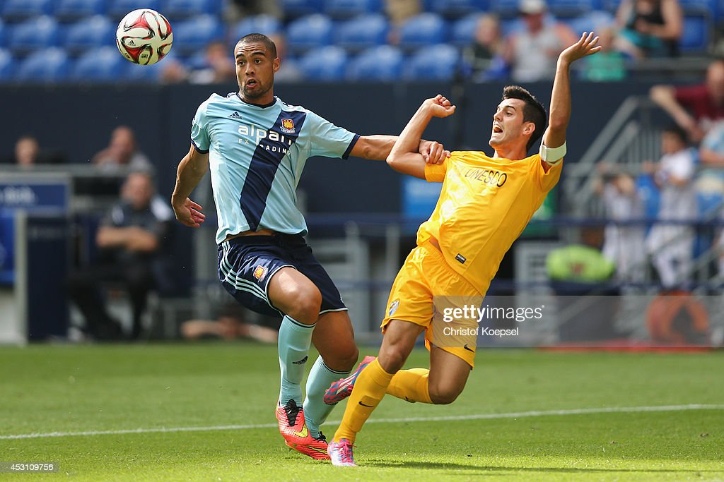 Winston Reid of West Ham United challenges Juanmi of Malaga during the match between FC Malaga and West Ham United as part of the Schalke 04 Cup Day at Veltins-Arena on August 3, 2014 in Gelsenkirchen, Germany.
