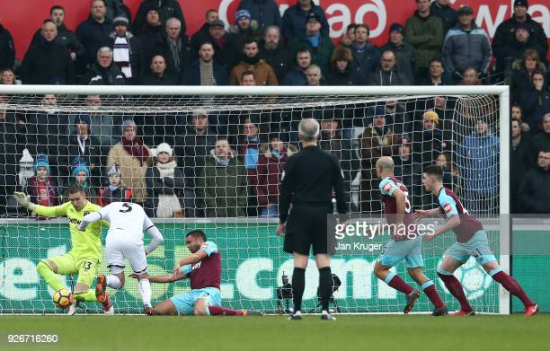 Winston Reid of West Ham United sustains an injury in a scrabble for the ball during the Premier League match between Swansea City and West Ham...