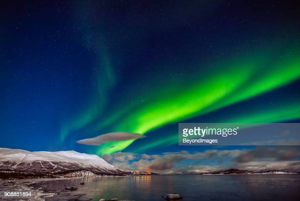 Winter: Awesome Aurora Borealis appears over Tornetrask Lake and Mount Nuolja in Swedish Lapland