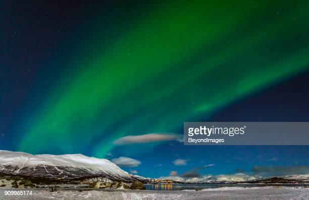 winter: awesome aurora borealis appears over tornetrask lake and mount nuolja in swedish lapland - norrbotten province stock photos and pictures