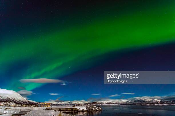 winter: awesome aurora borealis appears over tornetrask lake and mount nuolja in swedish lapland - norrbotten province stock pictures, royalty-free photos & images