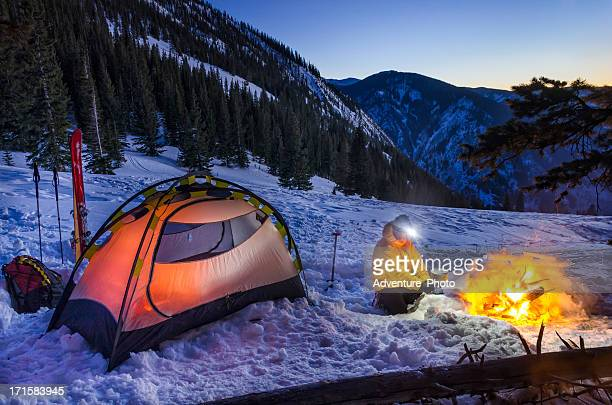 Winter Backcountry Camp with Man Cooking on Gas Stove