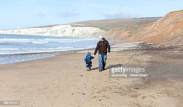 winter beach walk with dad - totland bay stock pictures, royalty-free photos & images